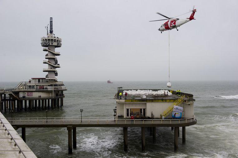 Foto uit december 2011 toont een helicopter die is ingezet om ruim honderd zakken puin af te voeren vanaf de pier in Scheveningen. De zakken tussen de 300 en 500 kg per stuk bevatten de resten van het Van der Valk-restaurant dat in het voorjaar van 2011 afbrandde. Beeld anp