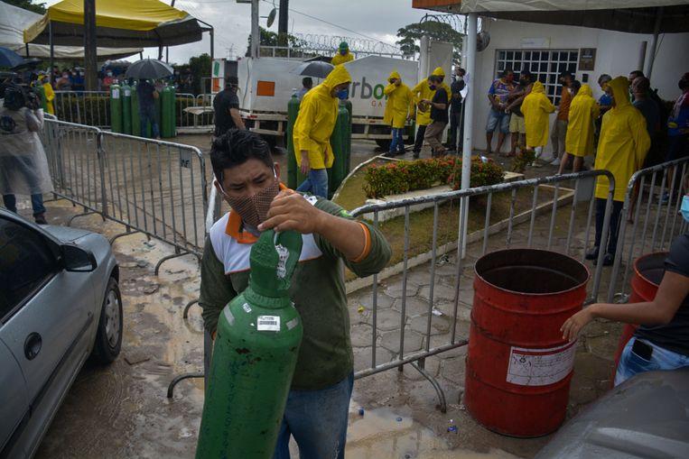 Mensen staan soms tot twaalf uur in de rij om zuurstoftanks bij te vullen om hun zieke naasten te redden. Beeld AFP