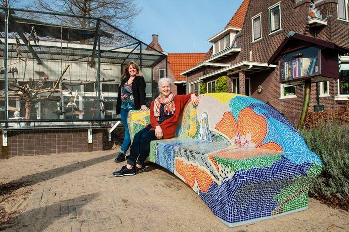 Marianne Waalwijk (zittend) en Manon Vonk met de mozaïekbank bij de volière in het Van Bergen IJzendoornpark, waar zij een belangrijke bijdrage aan hebben geleverd.