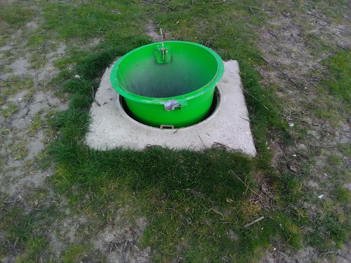 Van de ondergrondse afvalcontainers zijn sloten opengemaakt en de groene  kegels andersom geplaatst.