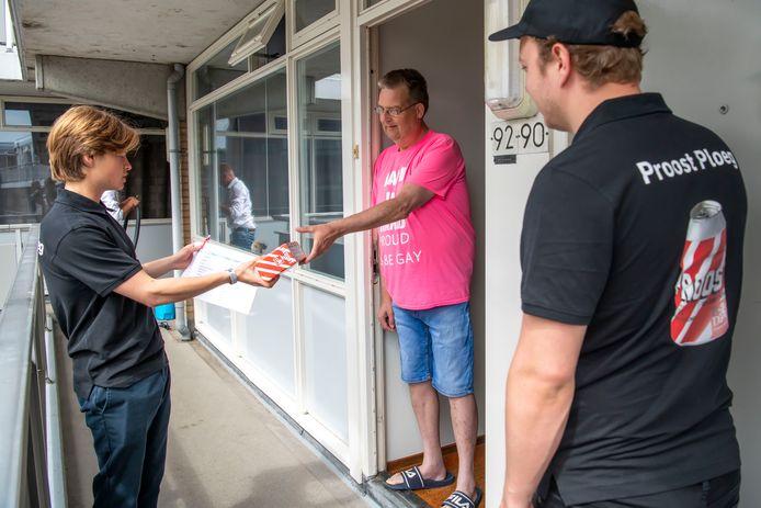 Het proostteam overhandigt een bierpakketje aan trouwe abonnee Frank Visser uit Tilburg.