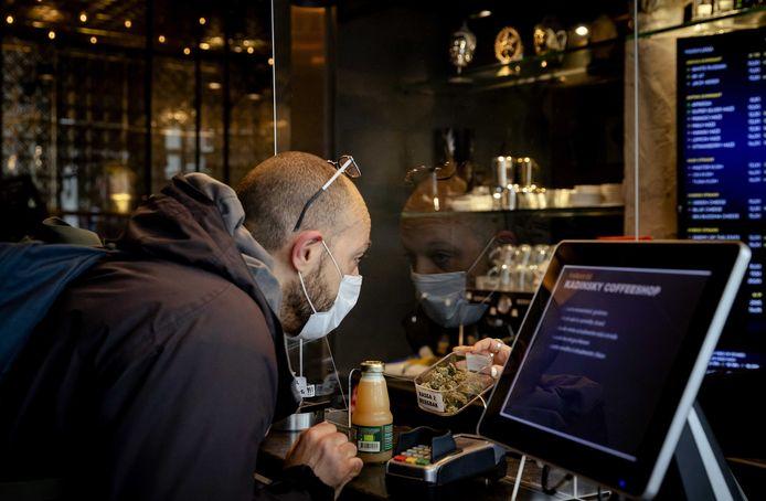 Een klant haalt producten op in coffeeshop Kadinsky in Amsterdam. Net als horecagelegenheden moeten coffeeshops in Nederland gesloten blijven volgens de nieuwe coronamaatregelen. Er mogen tot 20 uur nog wel producten worden afgehaald.