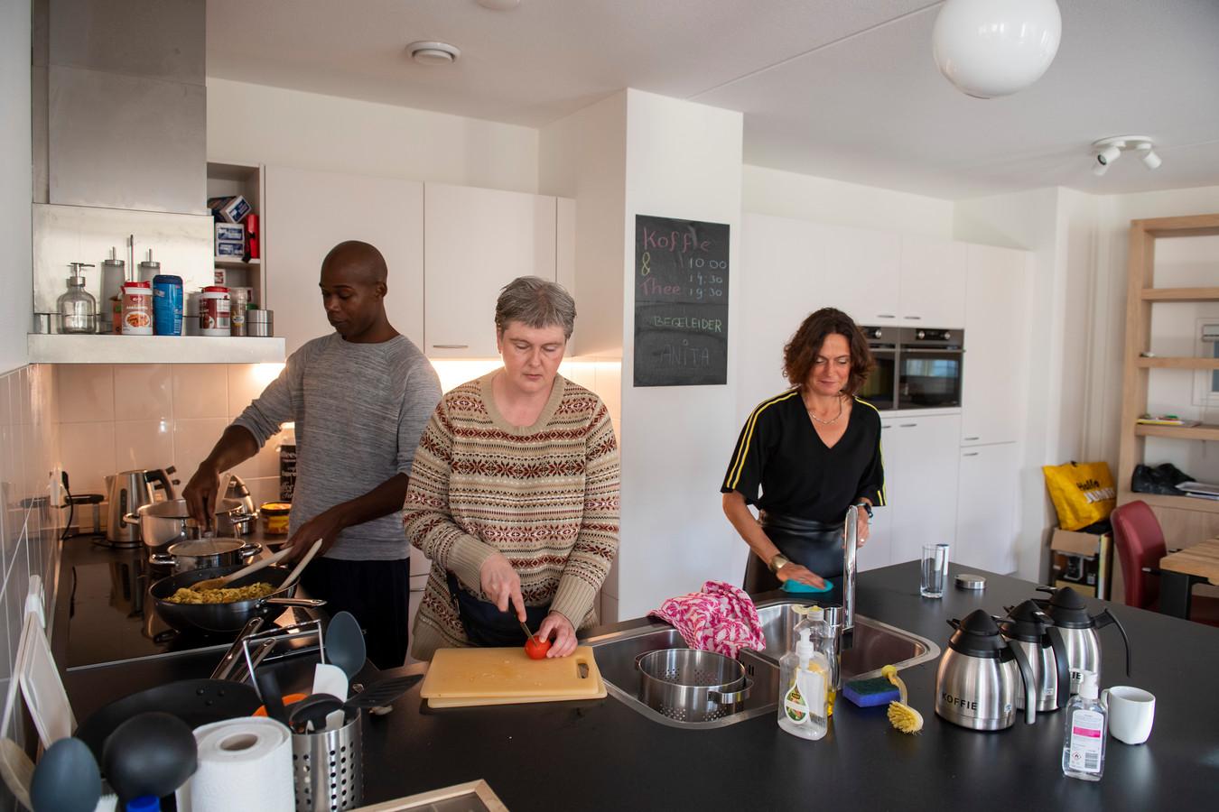 In de keuken van Chapeau in Tilburg: Ixor maakt bami met assistentie van Sandra. Rechts teamleidster Loes Verstappen.