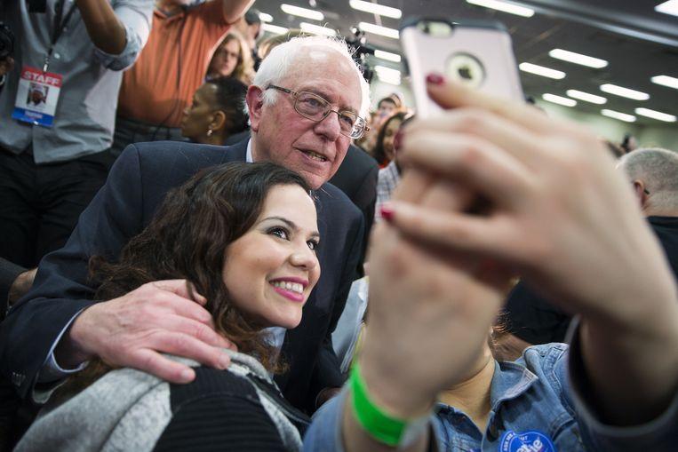 De Democratische presidentskandidaat Bernie Sanders poseert in het plaatsje Waterloo in Iowa voor een selfie. In tegenstelling tot rivaal Hillary Clinton, scoort Sanders goed onder jonge kiezers vanaf 18 jaar. Beeld AP