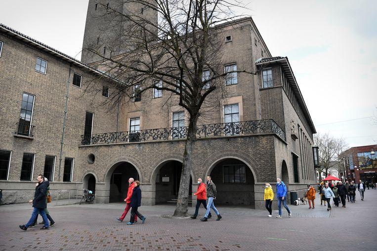 Mensen betuigen steun aan Pieter Omtzigt door rondjes te lopen rond het gemeentehuis in Enschede, die plaats waar Omtzigt woont. Beeld Marcel van den Bergh / de Volkskrant