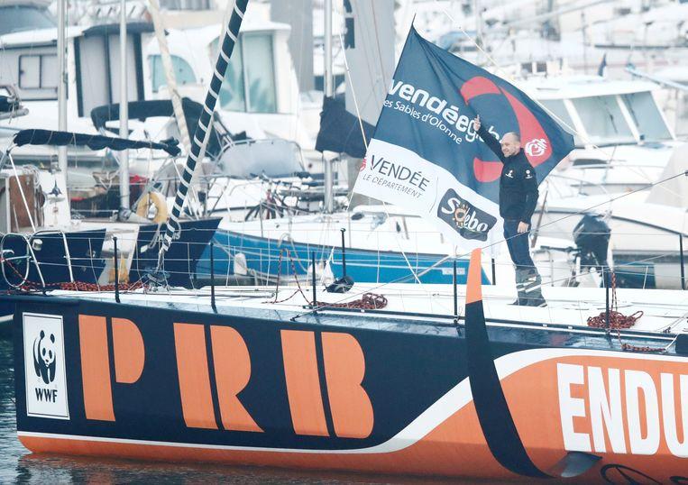 Een zwaaiende Kevin Escoffier op zijn schip in de haven van Les Sables-d'Olonne, startplaats van de Vendée Globe.  Beeld Reuters