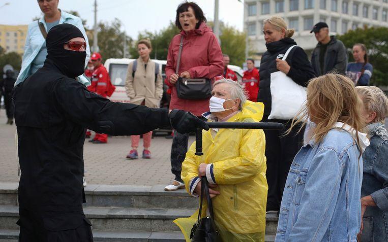 Vrouwen wijzen een politieman terecht tijdens een demonstratie tegen het regime in Minsk.  Beeld AP