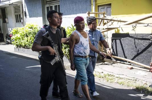 De Indonesische politie is een klopjacht begonnen op terroristen. Hier wordt een man in Soerabaja meegenomen voor verhoor.