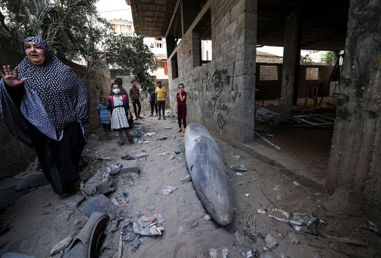 Een Palestijnse vrouw staat naast een niet-ontplofte bom van een Israëlisch gevechtsvliegtuig in een wijk in Gaza. Beeld AFP