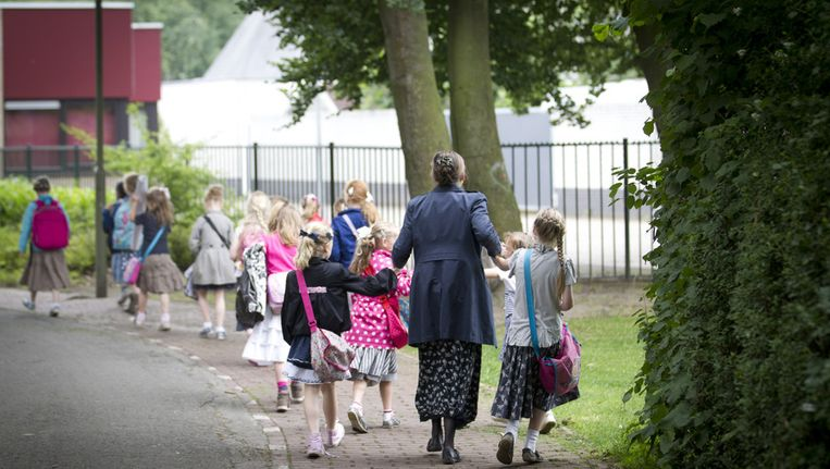 Moeders brengen kinderen naar de reformatorische basisschool Eben-Haezer in Barneveld, waar in een kleuterklas vermoedelijk kinderen met mazelen waren besmet. (Archieffoto juni 2013) Beeld anp