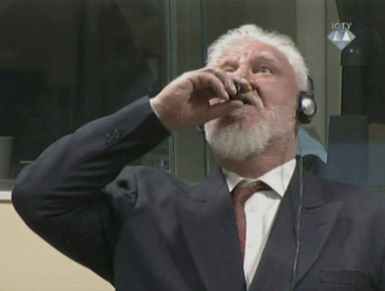 Slobodan Praljak drinkt van een gif tijdens zijn rechtszaak voor het Tribunaal in Den Haag. Beeld REUTERS