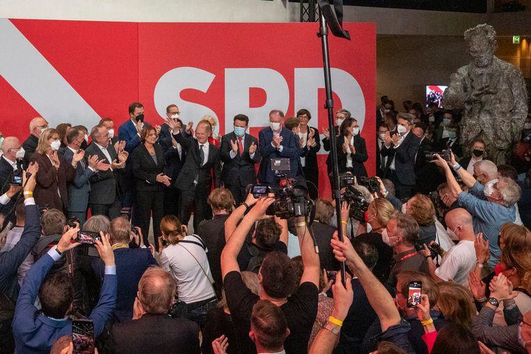 Olaf Scholz, leider van de Duitse sociaaldemocraten, zwaait in Berlijn naar aanhangers kort nadat bekend is geworden dat de SPD als grootste partij uit de bus is gekomen. Beeld Getty Images