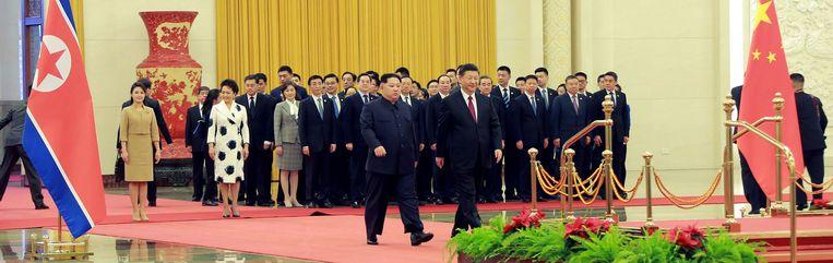 ► De Chinese president Xi Jinping (r.) en de Noord-Koreaanse leider Kim Jong-un tijdens een verwelkomingsceremonie in de Grote Hal van het Volk in Peking. Beeld AFP