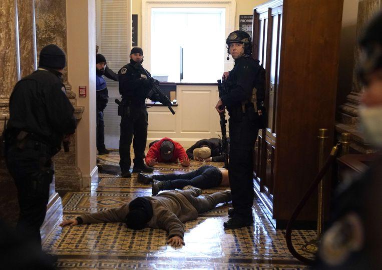 De Capitol Police dwingt betogers op de grond te liggen nadat ze het gebouw hebben bestormd. Beeld AFP