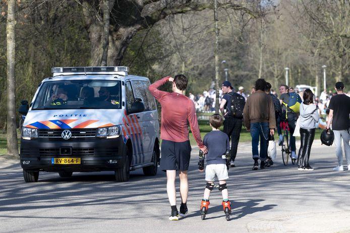 Politietoezicht in het Vondelpark. De toegang tot het park is tijdelijk afgesloten omdat het te druk is. Mensen mogen het park alleen nog uit.