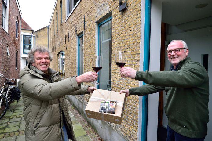 Frans de Jong (links) bezorgt een Flipse-borrelpakket bij René Brouwer. De fans van de twaalf jaar geleden overleden hond klinken nu thuis op haar in plaats van in café Kamphuisen.