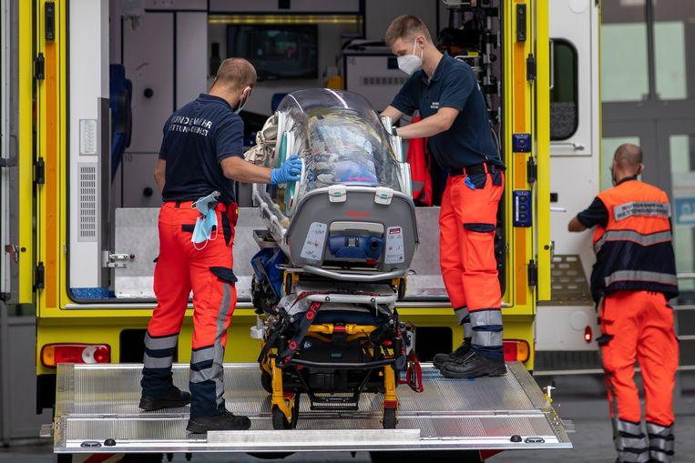 Ambulancepersoneel in Berlijn laadt de isoleerunit in waarmee Navalny in augustus vervoerd werd nadat hij onder leiding van Maksimisjin in Omsk in coma was gebracht.  Beeld Getty Images