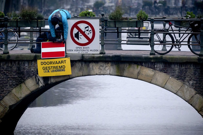 De gemeente Amsterdam heeft de Eenhoornsluis afgesloten, zodat er in de grachten ijs kan ontstaan.  Beeld ANP
