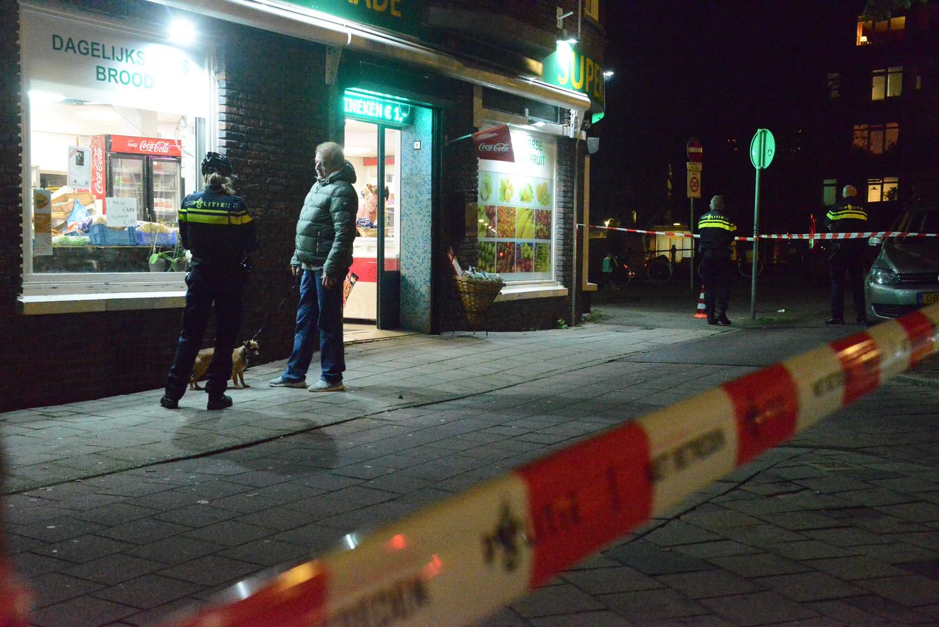 De politie doet onderzoek bij de overvallen supermarkt.