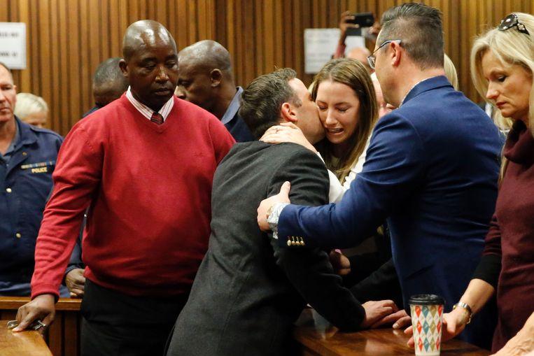 Oscar Pistorius kust zijn zus Aimee bij het verlaten van de rechtszaal.