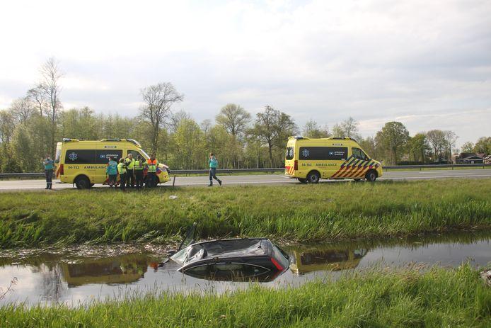 Bij Rouveen raakte een auto te water (voorgrond), waarna twee ambulances de gewonde inzittenden naar het ziekenhuis vervoerden.