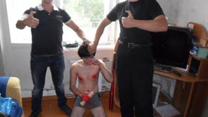 Een van de foto's die circuleert op VK.com, de Russische variant van Facebook. De jongen met ontbloot boven lichaam werd online naar een afspraakje gelokt en werd daarna door de mannen op de foto 'aangepakt'.