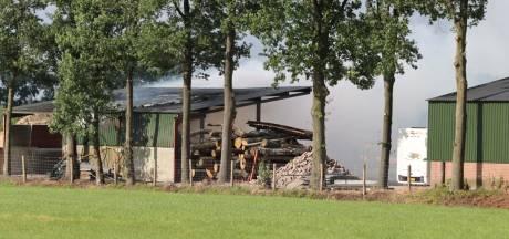 Shovel rijdt brandende boomstammen uit half open schuur in Achterveld