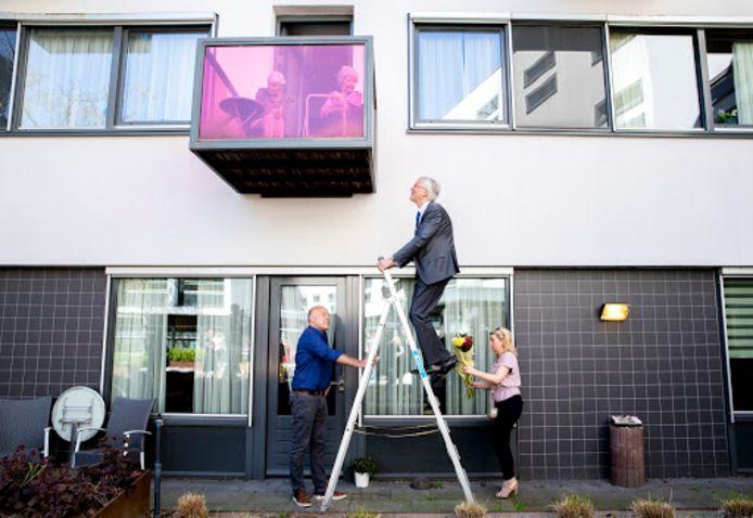 De burgemeester van Tilburg Theo Weterings neemt de afstandsmaatregel van anderhalve meter in acht en overhandigt via een ladder bloemen aan een bewoonster van een zorginstelling.