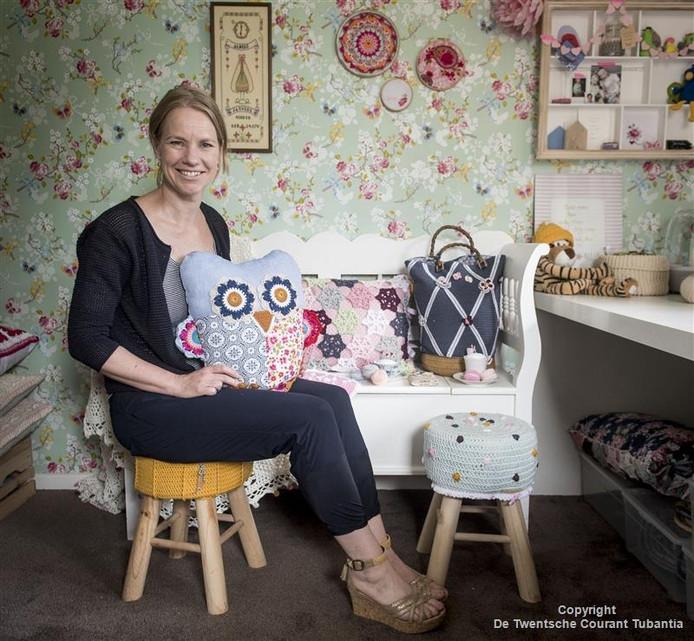"""Janneke Assink in haar werkkamer met kleurige tassen, kussens en krukjes. """"Ik kan er al mijn creativiteit in kwijt.''"""