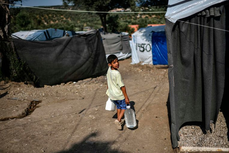 Een jongen draagt een fles water in een vluchtelingenkamp in Moria, op het Griekse eiland Lesbos. Beeld AFP
