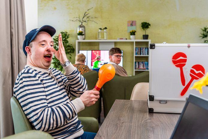 In Zwammerdam speelt Jan geconcentreerd mee met de Jostiband (livestream), maar hij heeft ook tijd voor een geintje. Op tafel de koffers die over groepswoningen zijn verspreid.