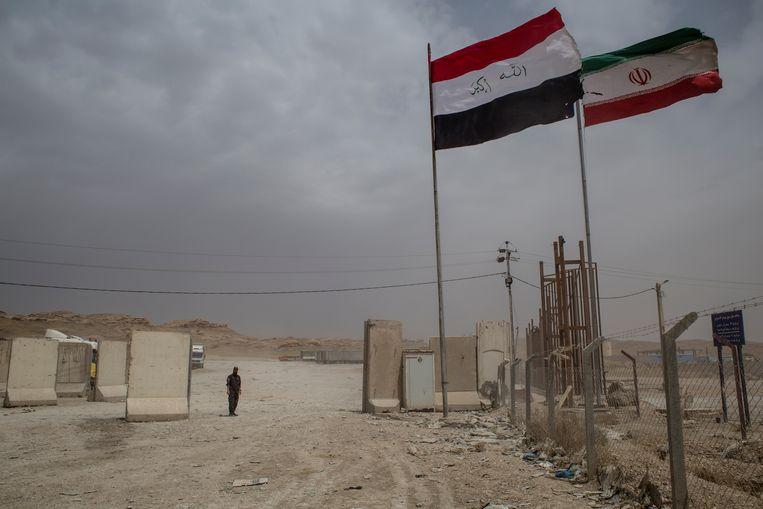 De grensovergang met Iran bij de Iraakse stad Mandali. Links de Iraakse vlag, rechts de Iraanse.  Beeld Hawre Khalid