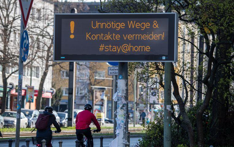 'Vermijd onnodige tripjes en contacten,' staat op een bord in Berlijn. Beeld AFP