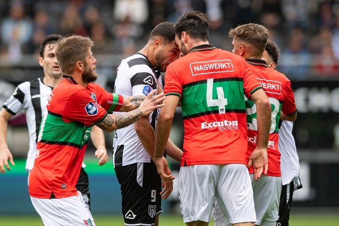 NEC-verdediger Iván Márquez en Heracles Almelo-spits Sinan Bakis staan met de hoofden tegen elkaar aan en Bakis krijgt daarvoor zijn tweede gele kaart.