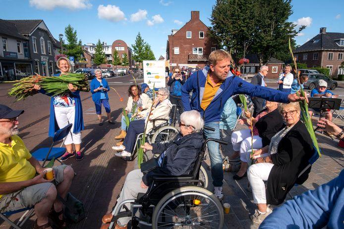 Harm Edens en Hester van Aalst delen gladiolen uit. Foto: Gerard Burgers.