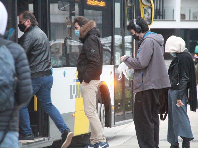 Politie controleert in burger op dragen mondmasker op de bus.