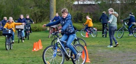 Leerlingen basisonderwijs volgen buiten les, want het is Nationale Buitenlesdag! In Volkel klimmen ze op de fiets, in Oss doen ze buiten-dictee