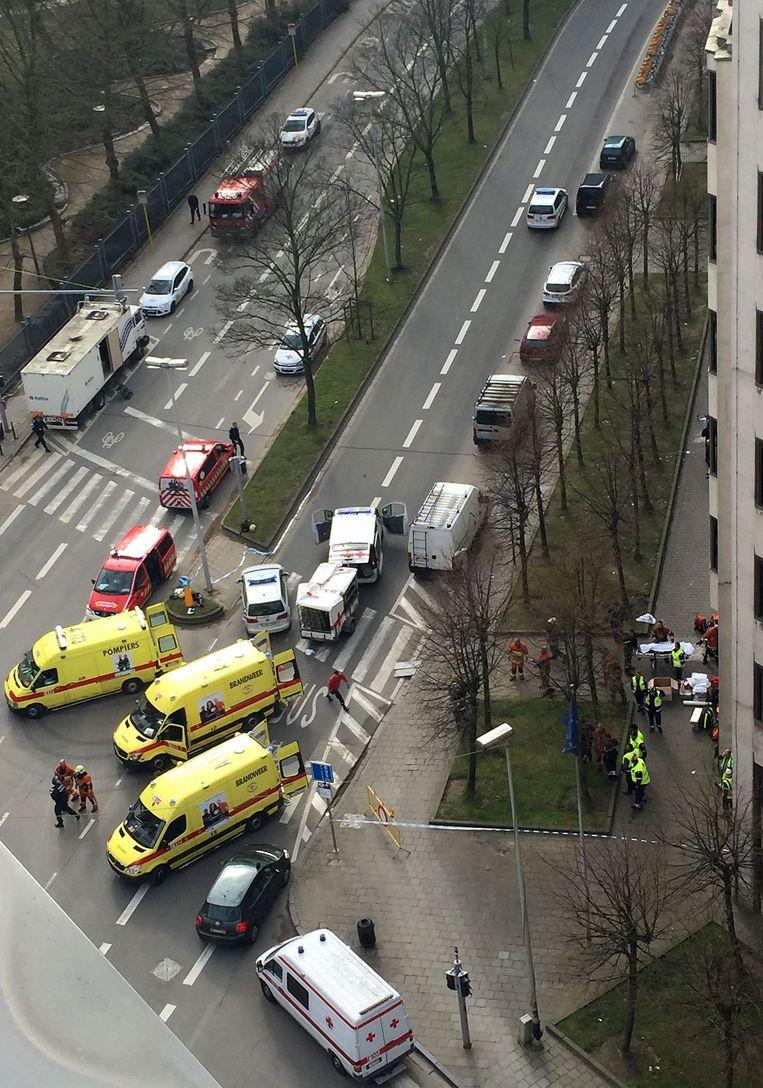 Hulpdiensten evacueren gewonde mensen buiten metrostation Maalbeek. Beeld afp