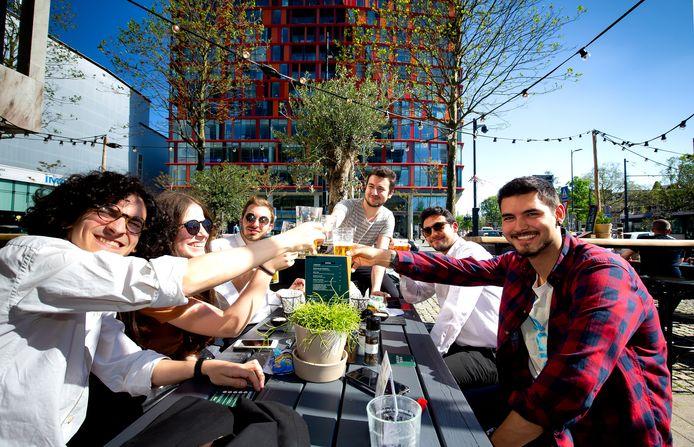 Een groep vrienden geniet van het mooie weer op een terras in Rotterdam.