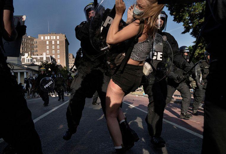 Een politieagent duwt een demonstrant aan de kant in een poging Lafayette Park in Washington D.C. te ontruimen.  Beeld REUTERS