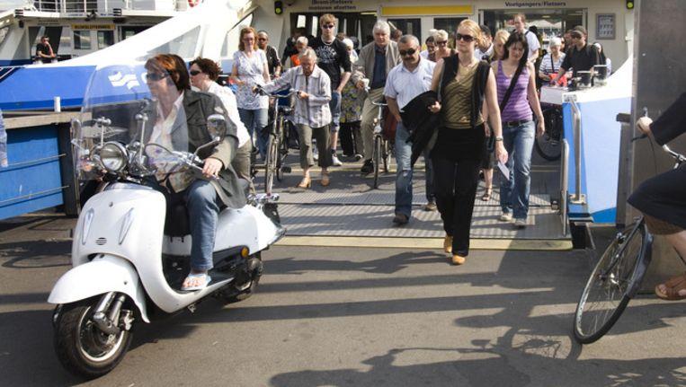 Een scooterrijder stuurt van de pont af. Beeld anp