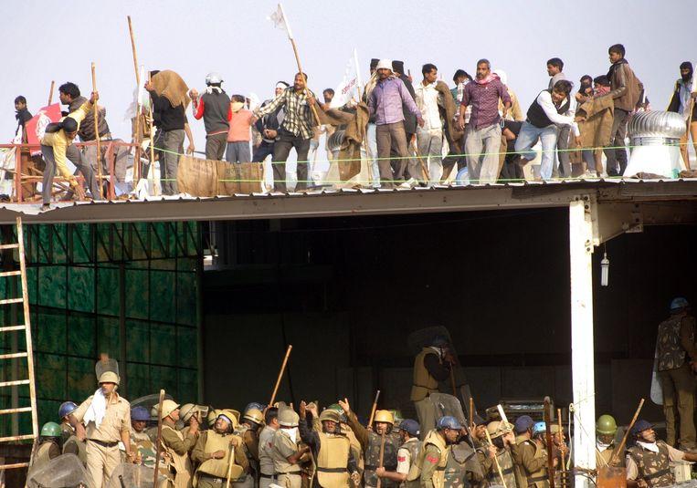 De aanhangers van de goeroe staan op het dak van zijn ashram, terwijl politieagenten het gebouw proberen binnen te dringen. Beeld AFP