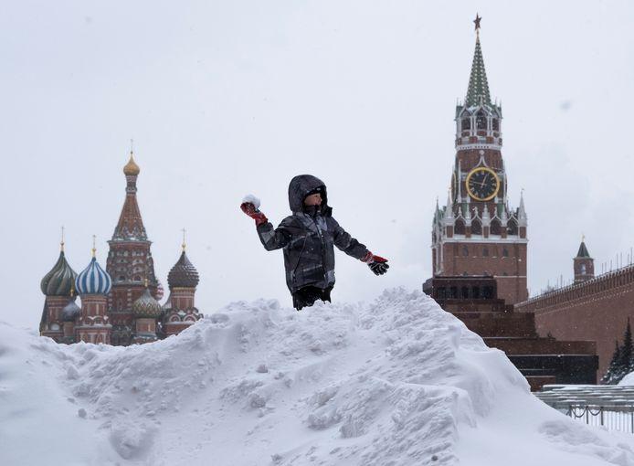 Een jongen speelt met de sneeuw op het Rode plein.