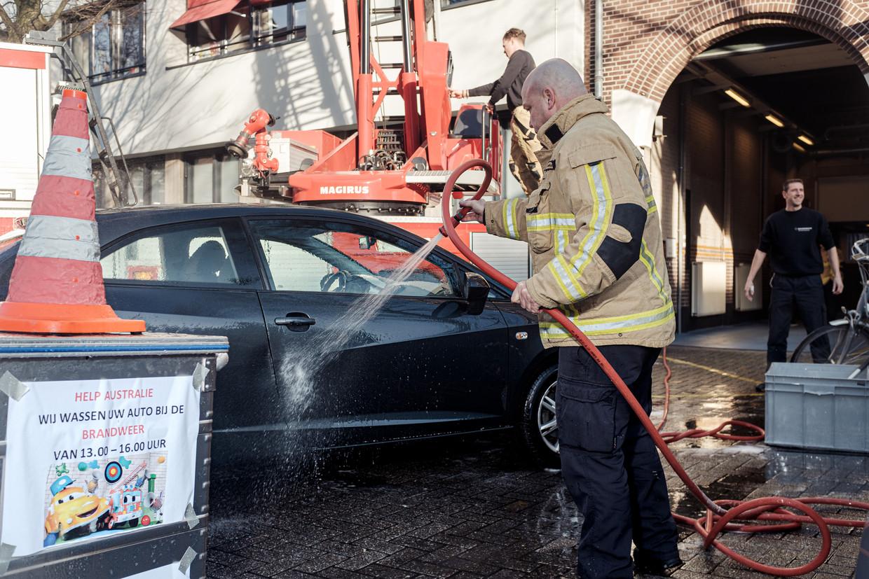 Brandweerlieden wassen auto's bij kazerne Victor.