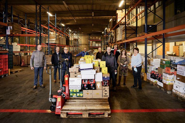De vrijwilligers van de Voedselbank in Kortrijk maken paletten klaar om verdeeld te worden. Beeld © Eric de Mildt