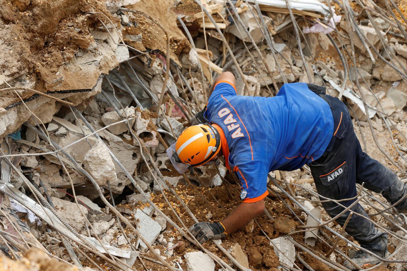 Een Turkse reddingswerker zoekt naar overlevenden.