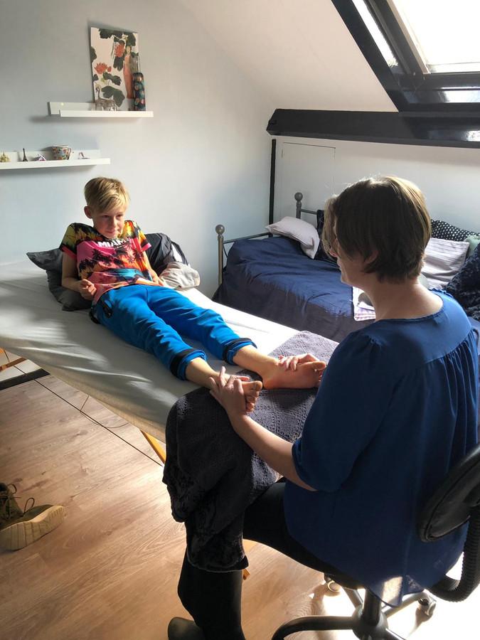 Bianca Kievit neemt een jongen onder handen. Ze werkt vanuit huis. ,,Dat kost me minder energie, want blind zijn kost veel energie.''