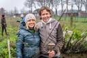 Kestrel Maher en Geert-Jan van Nistelrooij voor het veld waar vrijwilligers - in de achtergrond- weer een flinke hoeveelheid bomen voor het voedselbos aanplanten.