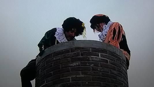 Een witte Piet duikt in de schoorsteen.