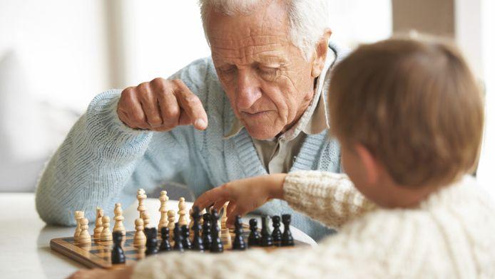 Een oude man speelt een schaakpartij met zijn kleinzoon. Het brein van oude mensen werkt trager omdat het meer informatie moet verwerken.